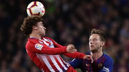 Striker Atletico Madrid, Antoine Griezmann, duel udara dengan gelandang Barcelona, Ivan Rakitic, pada laga La Liga di Stadion Camp Nou, Sabtu (6/4). Barcelona menang 2-0 atas Atletico Madrid. (AP/Manu Fernandez)