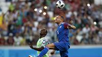 Pemain Islandia, Sverrir Ingason (kanan) membuang bola dari kejaran pemain Nigeria, Odion Ighalo pada laga grup D Piala Dunia 2018 di Volgograd Arena, Volgograd, Rusia, (22/6/2018). Nigeria menang 2-0.  (AP/Darko Vojinovic)