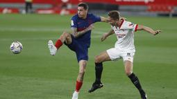 Pemain Atletico Madrid, Jose Gimenez, berebut bola dengan pemain Sevilla, Luuk de Jong, pada laga Liga Spanyol di Stadion Ramon Sanchez-Pizjuan, Minggu (4/4/2021). Sevilla menang dengan skor 1-0. (AP Photo/Angel Fernandez)
