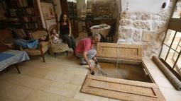Tal bersama keluarga saat berada diruang tamu menuju pintu masuk kolam ritual Yahudi (Mikveh) di Ein Karem, Yerusalem (1/7/2015). Tal menemukan Mikveh yang diyakini berusia lebih dari 2.000 tahun saat sedang merenovasi rumah.  (AFP/GALI TIBBON)