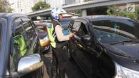 Aparat kepolisian mensosialisasikan perluasan ganjil genap kepada pengendara mobil di kawasan Tomang, Jakarta, Senin (2/7). Dinas Perhubungan DKI  mengerahkan 185 petugas untuk memantau uji coba perluasan ganjil genap. (Liputan6.com/Arya Manggala)