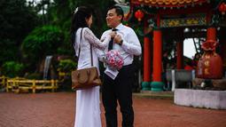Salah satu pasangan keturunan Tionghoa bersiap mengikuti acara pernikahan massal di Kuil Thean Hou, Kuala Lumpur, Senin (9/9/2019). Upacara pernikahan massal diadakan untuk 99 pasangan pada hari kesembilan bulan kesembilan yang dianggap sebagai tanggal keberuntungan. (Mohd RASFAN / AFP)
