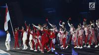 Parade atlet Indonesia saat upacara Penutupan Asian Games 2018 di Stadion Utama Gelora Bung Karno, Jakarta, Minggu (2/9). Mereka mengenakan jas hujan yang mengguyur Jakarta. (Liputan6.com/Helmi Fithriansyah)