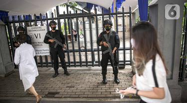 Personel kepolisian bersenjata lengkap melakukan penjagaan di gerbang masuk Gereja Katedral, Jakarta, Kamis (1/4/2021). Sebanyak 150 personel gabungan TNI, Polri dan Satpol PP melakukan pengamanan jelang rangkaian perayaan Hari Paskah di gereja tersebut. (Liputan6.com/Faizal Fanani)
