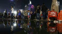 Warga memadati malam pergantian tahun di kawasan Bundaran HI, Jakarta, Minggu (31/12). Pemprov DKI Jakarta memberlakukan car free night di Jalan Sudirman hingga Thamrin. (Liputan6.com/Angga Yuniar)