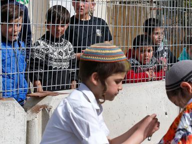 Anak-anak Palestina menyaksikan warga Yahudi merayakan Hari Purim di Jalan al-Shuhada, Kota Hebron, Tepi Barat, Kamis (1/3). Hari Purim diperingati untuk memperingati pembebasan orang-orang Yahudi dari genosida Persia kuno. (AFP PHOTO/HAZEM BADER)