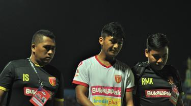 Bek Badak Lampung, Zaenal Haq didampingi tim medis setelah tidak bisa melanjutkan pertandingan melawan Arema FC. (Bola.com/Iwan Setiawan)