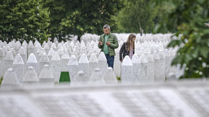 Seorang pria berdoa di pemakaman korban pembantaian Sreberenica, Potocari, Bosnia, 7 Juli 2020. Lebih dari 8.000 muslim Bosnia tewas dalam 10 hari pembantaian setelah kota itu dikuasai pasukan Serbia pada bulan-bulan terakhir perang saudara 1992-1995. (AP Photo/Kemal Softic)