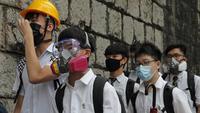 Para siswa sekolah mengenakan topeng dan helm berjalan di luar St. Paul's College selama protes di Hong Kong, Selasa (3/9/2019). Puluhan ribu siswa di Hong Kong memprotes terhadap gerakan anti-pemerintah. (AP Photo/Kin Cheung)