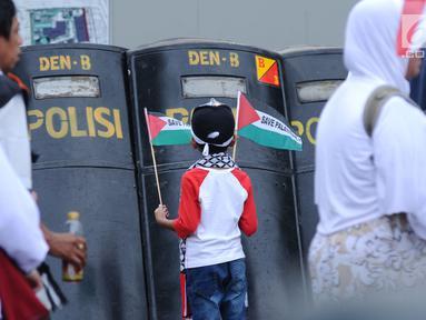 Seorang anak melihat tameng polisi saat mengikuti aksi dukungan bagi negara Palestina di depan Kedubes AS, Jakarta, Minggu (10/12). Mereka memprotes keputusan Presiden Trump yang mengakui Yerusalem jadi Ibu Kota Israel. (Liputan6.com/Helmi Fithriansyah)