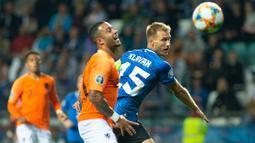 Bek Estonia, Ragnar Klavan, berebut bola dengan striker Belanda, Memphis Depay, pada laga Kualifikasi Piala Eropa 2020 di Talinn, Estonia, Senin (9/9). Estonia kalah 0-4 dari Belanda. (AFP/Raigo Pajula)