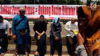 Sejumlah orang dari ormas Islam menggelar aksi unjuk rasa di depan Gedung DPR, Jalan Gatot Subroto, Jakarta, Selasa (24/10). Dalam aksi ini berbagai pesan disampaikan ribuan massa dalam bentuk tulisan seperti poster dan spanduk. (Liputan6.com/JohanTallo)