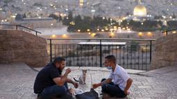 Dua pria Pelestina berbuka puasa selama bulan suci Ramadan dengan latar belakang Kota Tua Yerusalem dan kompleks Masjid al-Aqsa yang ditutup selama krisis pandemi coronavirus yang baru di Bukit Zaitun (19/5/2020). (AFP/Ahmad Gharabli)