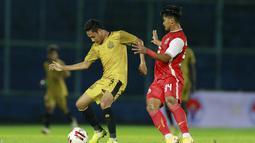 Gelandang Bhayangkara Solo FC, Evan Dimas (kiri) berebut bola dengan striker Persija Jakarta, Heri Susanto dalam laga matchday ke-3 Grup B Piala Menpora 2021 di Stadion Kanjuruhan, Malang, Rabu (31/3/2021). (Bola.com/M Iqbal Ichsan)