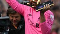 Kiper Liverpool, Alisson Becker menyapa para fans saat memegang penghargaan Golden Gloves usai pertandingan melawan Wolverhampton Wanderers pada lanjutan Liga Inggris di Anfield, Inggris (12/5/2019). Alisson mencatatkan 21 clean sheet di sepanjang musim ini. (AFP Photo/Paul Ellis)