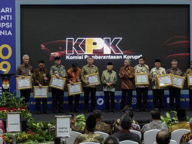 Wakil Presiden Ma'ruf Amin didampingi Ketua KPK Agus Rahardjo berfoto bersama penerima penghargaan saat acara Hari Anti Korupsi Dunia (Hakordia) 2019 di Gedung Penunjang KPK, Jakarta, Senin (9/12/2019). Hari Antikorupsi Sedunia diperingati setiap 9 Desember. (Liputan6.com/Faizal Fanani)