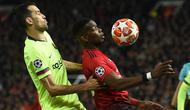 Gelandang Barcelona, Sergio Busquets berebut bola dengan gelandang Manchester United, Paul Pogba pada leg pertama perempat final Liga Champions di Stadion Old Trafford, Rabu (10/4). Barcelona menang tipis 1-0 atas Manchester United. (Oli SCARFF / AFP)