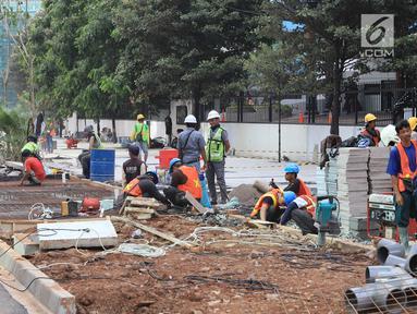 Pekerja menyelesaikan jalur pedestrian di Jalan Sudirman, Jakarta, Senin (2/7). Perbaikan jalur pedestrian di sepanjang koridor Jalan Sudirman menjadi porsi pekerjaan PT MRT Jakarta, ditargetkan selesai pada 31 Juli 2018. (Liputan6.com/Arya Manggala)