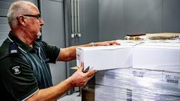 Petugas bea cukai memeriksa kotak berisi botol vodka setelah disita di pelabuhan Rotterdam, Belanda, Selasa (26/2). Sebanyak 90.000 botol vodka itu diyakini bakal dikirim untuk pemimpin Korut, Kim Jong-un dan kepala pasukannya. (Robin UTRECHT/ANP/AFP)