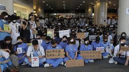 Perawat dan staf medis saat unjuk rasa rasa di sebuah rumah sakit di Hong Kong (13/8/2019). Para pemrotes berunjuk rasa menentang kebrutalan polisi pada aksi-aksi demonstrasi akhir pekan. (AP Photo/Kin Cheung)