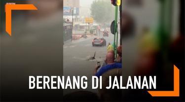 Sebelum membantu pengguna jalan yang mengalami kesulitan saat banjir, pria ini malah berenang terlebih dahulu. Aksinya pun mengundang tawa warga.