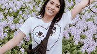 Aktris Tyas Mirasih berfoto dengan latar bunga eceng gondok di Taman Cinta Teluk Jering, Kampar. (dok. Istagram @tyasmirasih/M Syukur)