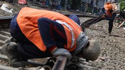 Pekerja mengukur bantalan rel kereta di kawasan Roxy, Jakarta, Selasa (7/1). Penambahan kerikil tersebut dilakukan sebagai bentuk perawatan rutin agar perjalanan kereta tetap aman dan lancar. (Liputan6.com/Immanuel Antonius)