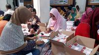 Tenaga lepas di kantor KPU Kota Malang melipat dan menyortir surat suara Pilkada serentak 2018 (Liputan6.com/Zainul Arifin)
