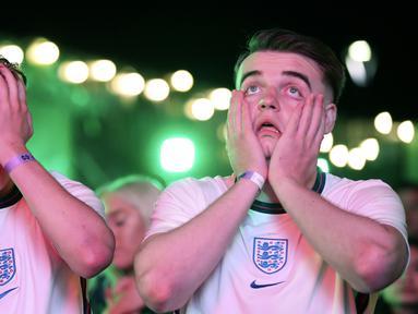 Suporter Inggris bereaksi setelah Italia memenangkan pertandingan final Euro 2020 di zona penggemar di Newcastle, Inggris, Minggu (11/7/2021). Italia menang 3-2 lewat adu penalti dengan Inggris usai bermain imbang 1-1 di waktu normal. (AP Photo/Scott Heppell)