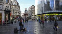 Pembeli berjalan kaki membawa tas belanjaan di Leicester Square setelah pelonggaran pembatasan virus corona COVID-19 menyusul berakhirnya kebijakan penguncian nasional atau lockdown kedua di Inggris, di London, Sabtu (5/12/2020). (AP Photo/Alberto Pezzali)