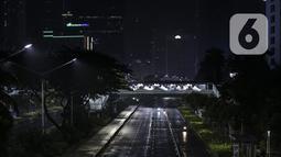 Warga menyeberang saat diberlakukannya Car Free Night dan Crowd Free Night di Jalan Sudirman-MH Thamrin, Jakarta (31/12/2020). Jalan Sudirman-MH Thamrin ditutup pada malam pergantian tahun untuk mencegah kerumunan warga. (Liputan6.com/Johan Tallo)