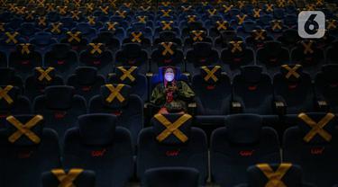 Penonton duduk dengan menjaga jarak di dalam bisokop CGV Grand Indonesia, Jakarta, Kamis (16/9/2021). Pemerintah memberikan kelonggaran dengan memperbolehkan bioskop buka kembali di wilayah berstatus PPKM level 3 dan 2 dengan kapasitas pengunjung 50 persen. (Liputan6.com/Faizal Fanani)