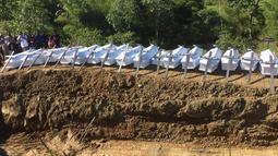 Peti mati korban banjir bandang siap untuk dimakamkan di Sentani, Kabupaten Jayapura, Papua, Rabu (27/3). Pemakaman massal tersebut merupakan permintaan Pemerintah Kabupaten Jayapura. (NETHY DHARMA SOMBA/AFP)
