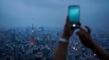 Gambar pada 19 Agustus 2019 memperlihatkan seorang turis mengambil gambar panorama skyline (kaki langit) kota Tokyo dari dek observasi Menara Roppongi Hills. Wisatawan dapat melihat berbagai gedung pencakar langit yang semua tertata rapi di kota terkenal sibuk ini. (AP Photo/Jae C. Hong)