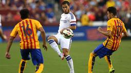Gelandang Chelsea, Eden Hazard mengumpan bola dari kejaran dua pemain Barcelona saat International Champions Cup 2015 di Landover, Maryland, Rabu (29/7/2015). Chelsea menang 4-2 lewat adu penalti, usai bermain imbang 2-2 waktu normal. (AFP/Patrick Smith)