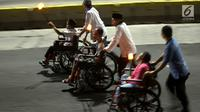 Umat muslim menggunakan kursi roda mengikuti pawai obor menyambut Tahun Baru Islam 1441 H di kawasan Bundaran HI, Jakarta, Sabtu (31/8/2019). Pawai yang diikuti 4000 peserta digelar dalam rangka Jakarta Muharram Festival. (merdeka.com/Imam Bukhori)