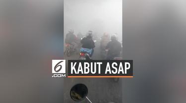 Kabut asap yang terjadi di Kalimantan menyebabkan jarak pandang pengendara motor terbatas. Hal ini membuat warga berhati-hati dan kesulitan melihat arus di jalanan.