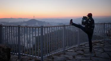 Seorang pejalan kaki mengabadikan kota Seoul dan menara Namsan dengan ponselnya selama matahari terbit di Korea Selatan (31/10). Seoul adalah ibu kota Korea Selatan yang berusia lebih dari 600 tahun. (AFP Photo/Ed Jones)
