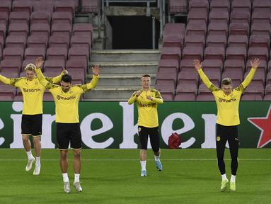 Para pemain Borussia Dortmund melakukan pemanasan saat mengikuti sesi latihan di stadion Camp Nou di Barcelona (26/11/2019). Dortmund akan bertanding melawan Barcelona pada Grup F Liga Champions. (AFP Photo/Josep Lago)