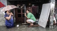 Warga berada di depan rumah saat banjir merendam permukiman Bukit Duri, Jakarta, Kamis (18/2/2021). Hujan deras yang mengguyur sejak pagi menyebabkan permukiman warga di 5 RW, yakni RW 03, 04, 05, 06, dan 07 Kelurahan Bukit Duri terendam banjir. (merdeka.com/Iqbal S Nugroho)