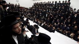 """Ratusan jemaat Yahudi Ultra-Orthodoks dari dinasti Belz Hasidic saat mengikuti perayaan Tu Bishvat, hari Arbor Yahudi di Jerusalem, (25/1). Tu Bishvat adalah salah satu dari empat """"Tahun Baru"""" yang disebutkan di Mishnah. (REUTERS/Baz Ratner)"""