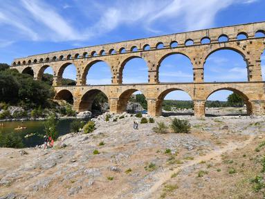 Pemandangan Pont du Gard atau Jembatan Gard di Vers-Pont-du-Gard, Prancis, Rabu (21/8/2019). Pont du Gard adalah jembatan saluran air Romawi yang merupakan bagian dari daftar situs warisan dunia UNESCO. (Pascal GUYOT/AFP)