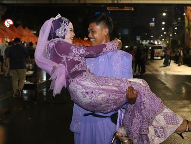 Pasangan Aldona Febrianti dan Septian Maulana meluapkan kebahagiaan usai ijab kabul di jalan MH Thamrin, Jakarta, Senin (31/12). 557 pasangan mengikuti nikah massal dan isbat nikah pada malam pergantian tahun 2018-2019. (Liputan6.com/Helmi Fithriansyah)
