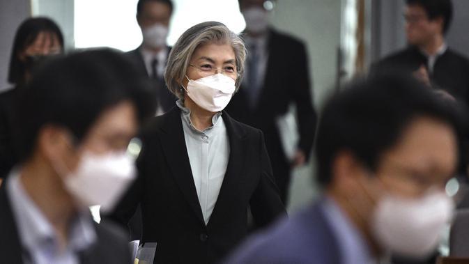 Menteri Luar Negeri Korea Selatan Kang Kyung-wha (tengah) mengenakan masker tiba untuk menghadiri konferensi untuk diplomat asing tentang situasi wabah virus corona di Korea, di kementerian luar negeri di Seoul, Jumat (6/3/2020). (Jung Yeon-je/Pool Photo via AP)