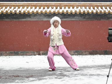 Seorang wanita merekam dirinya melakukan tai chi ketika salju turun di sebuah taman di Beijing (16/12/2019). Salju yang melanda Beijing Senin pagi membuat penerbangan dibatalkan dan rute bus disesuaikan. (AFP Photo/Wang Zhao)