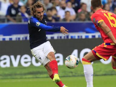 Penyerang Prancis, Antoine Griezmann menendang bola dari kawalan pemain Andorra, Moises San Nicolas pada pertandingan grup H Kualifikasi Euro 2020 di Stade de France di Saint Denis, Paris (10/9/2019). Prancis menang telak 3-0 atas Andorra. (AP Photo/Michel Euler)