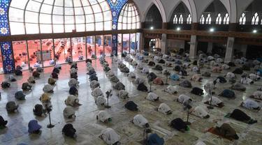 Umat muslim menerapkan jaga jarak aman atau physical distancing saat melaksanakan salat Jumat berjemaah selama Ramadan di Masjid Data Darbar, Lahore, Pakistan, Jumat (1/5/2020). Umat muslim dunia melaksanakan Ramadan tahun ini di tengah pandemi COVID-19. (ARIF ALI/AFP)