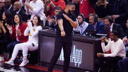 Rapper Drake berselebrasi saat menyaksikan pertandingan kelima Final NBA 2019 antara Golden State Warriors melawan Toronto Raptors di Scotiabank Arena, Toronto, Ontario (11/6/2019). Warriors memaksa Toronto Raptors memainkan gim keenam di NBA Final 2019. (Chris Young/The Canadian Press via AP)