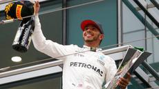 Pembalap Mercedes, Lewis Hamilton bersorak sambil memegang trofi Grand Prix (GP) China di Sirkuit Internasional Shanghai, Minggu (9/4). Hamilton finis pertama dengan catatan waktu 1 jam 37 menit 36,158 detik.(AP Photo/Toru Takahashi)