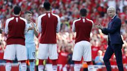 Pelatih Arsenal, Arsene Wenger, disambut para pemain saat perpisahan di Stadion Emirates (6/5/2018). Selama 22 tahun membesut Arsenal, Wenger telah mempersembahkan 17 gelar dan 704 Kemenangan. (AFP/Ian Kington)